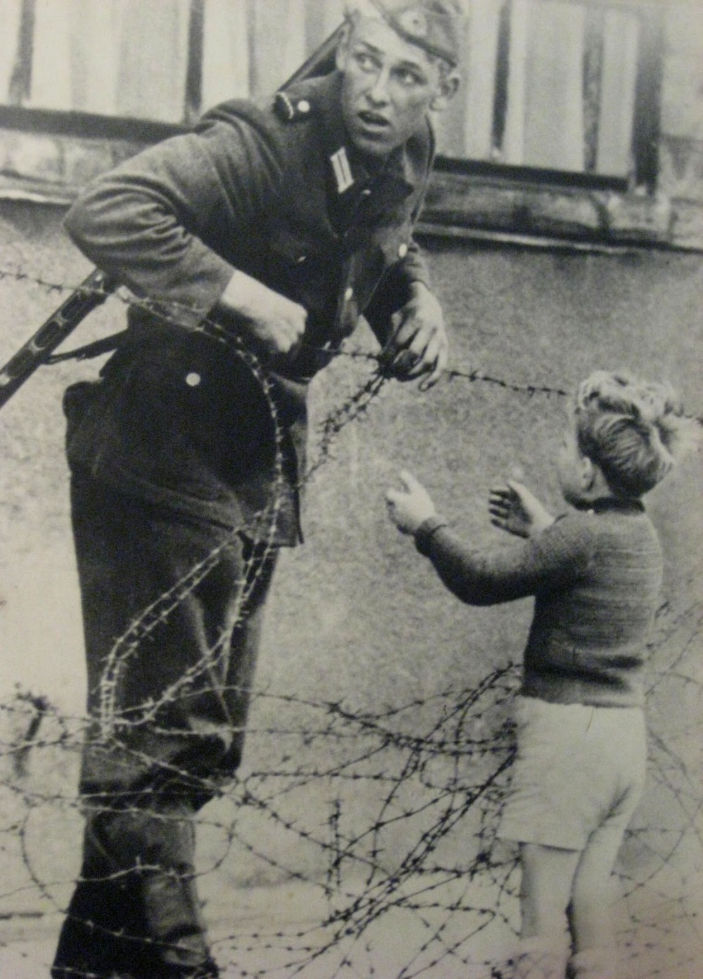 An E. German soldier helps a young boy cross the barbed wire which was a marker for where the Berlin Wall would soon be built.