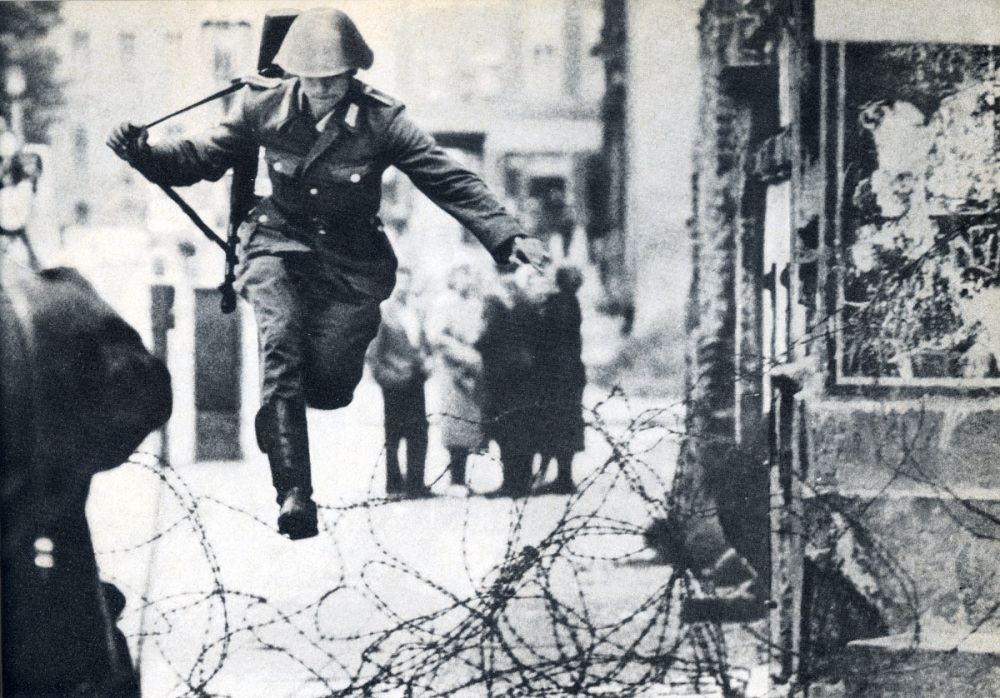 Conrad Schumann jumping a barbed wire fence at the Berlin Wall.